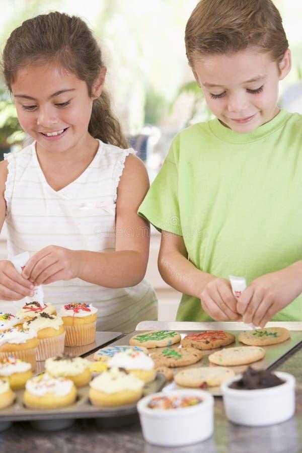 Twee kinderen die in keuken koekjes verfraaien royalty-vrije stock afbeelding