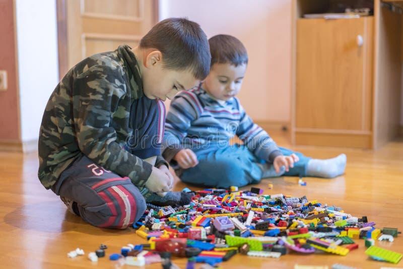 Twee kinderen die met veel de kleurrijke plastic zitting van de blokkenaannemer op een vloer spelen binnen Twee klein broersspel stock foto