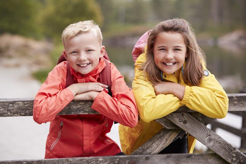 Twee kinderen die op een houten omheining in het platteland die aan camera leunen, sluiten omhoog glimlachen stock foto's