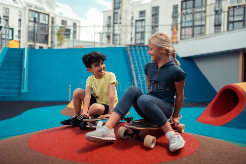 Twee kinderen die zitting op hun skateboards spreken royalty-vrije stock fotografie