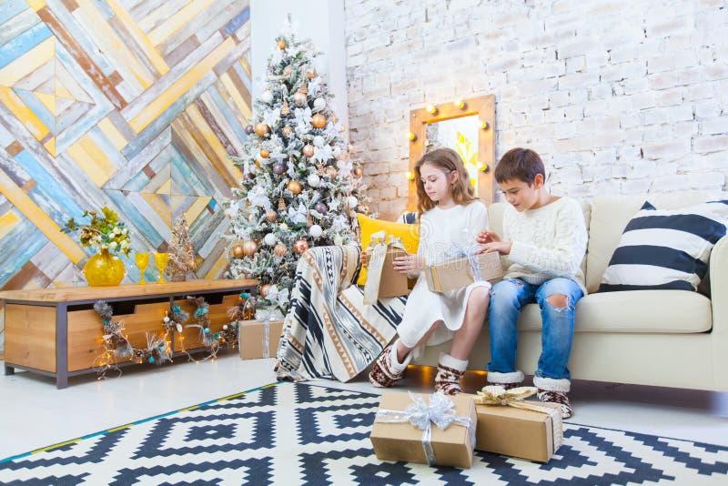 Twee kinderen een jongen en een meisje bij een Kerstboom op een bank met giften In lichte kleuren royalty-vrije stock fotografie