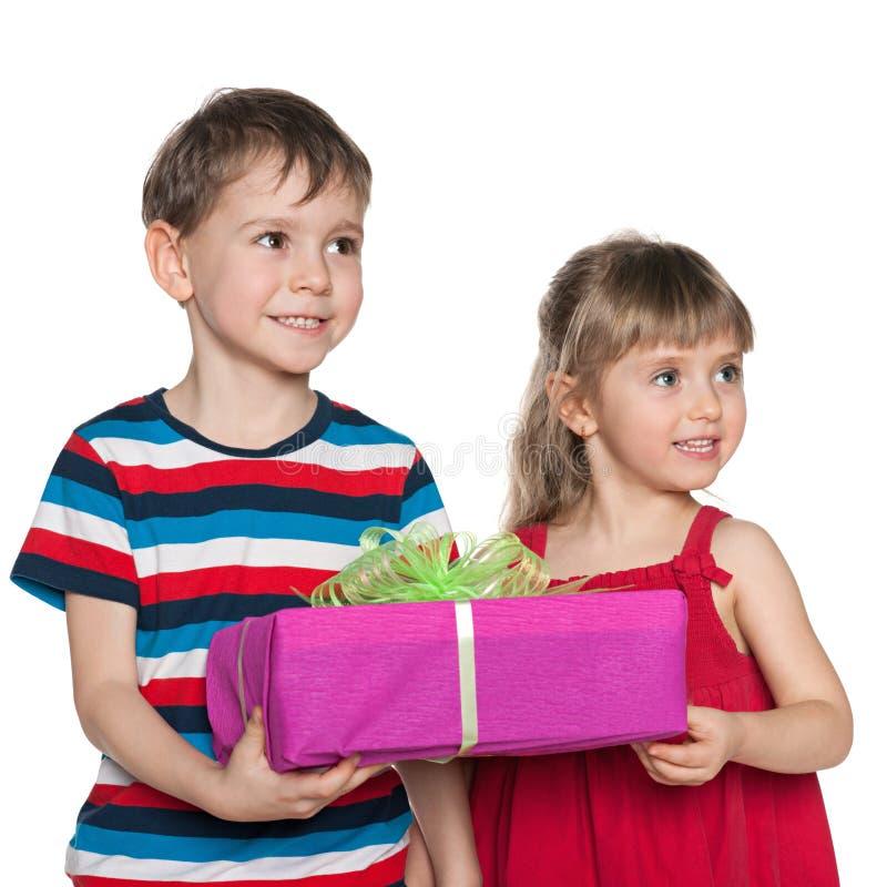 Twee kinderen houden een giftdoos stock afbeeldingen