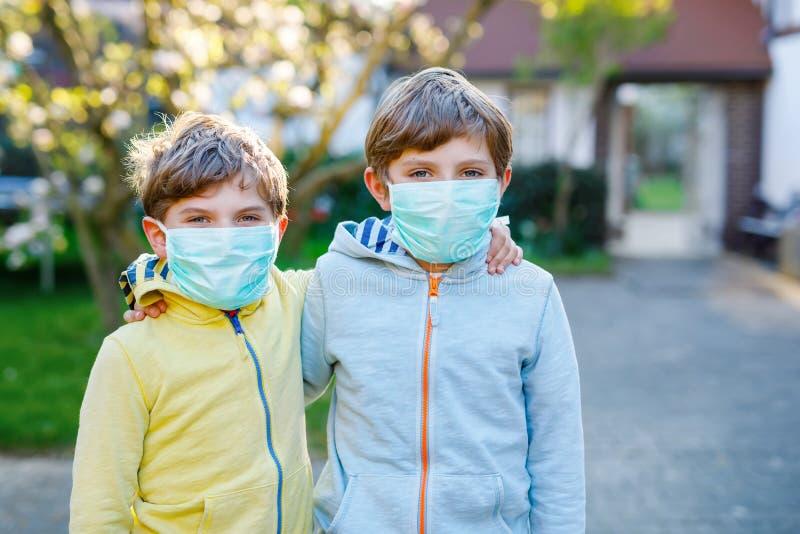 Twee kinderen jongens in het medisch masker als bescherming tegen een pandemische coronavirusziekte Kinderen, mooie broers en zus stock afbeelding