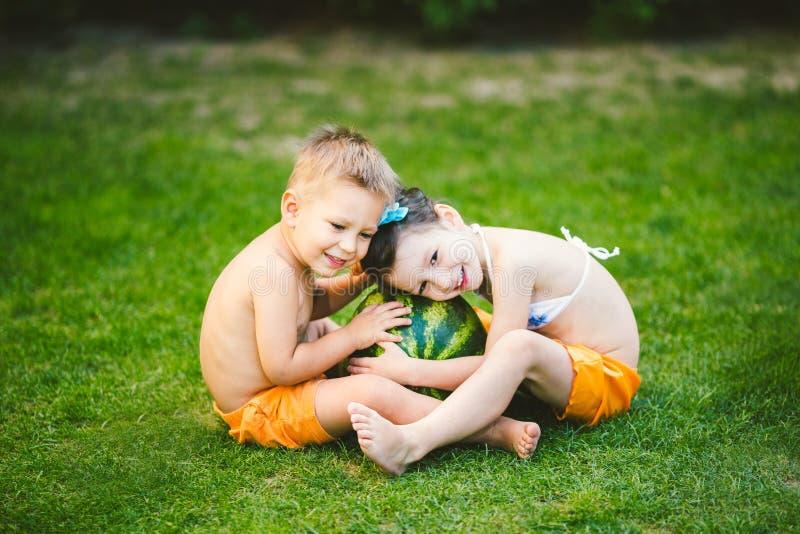 Twee kinderen, Kaukasische broer en zuster die, die op groen gras in binnenplaats van huis zitten en grote smakelijke zoete water royalty-vrije stock afbeelding