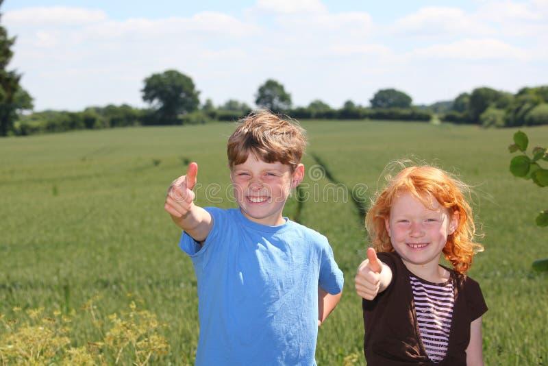 Twee kinderen met omhoog duimen stock afbeeldingen