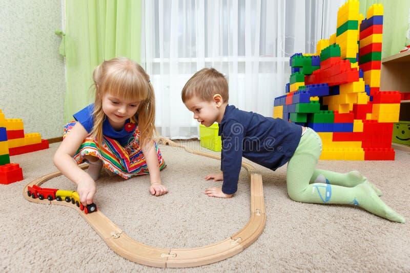 Twee kinderen spelen met stuk speelgoed spoorweg in kleuterschool royalty-vrije stock afbeelding