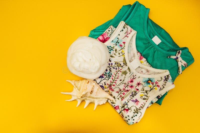 Twee kleding, witte bloem en grote shell op een gele geïsoleerde achtergrond, royalty-vrije stock fotografie