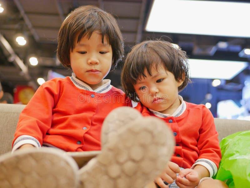 Twee klein Aziatisch babymeisje, zusters die, die en op een smartphone zitten letten samen, terwijl het wachten op haar moeder om royalty-vrije stock afbeelding