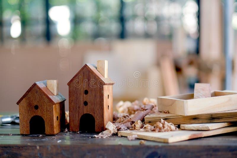 Twee klein houten huizen of nestkastje worden gezet op de lijst onder houten stapel en ander materiaal om in de ruimte met zacht  stock foto