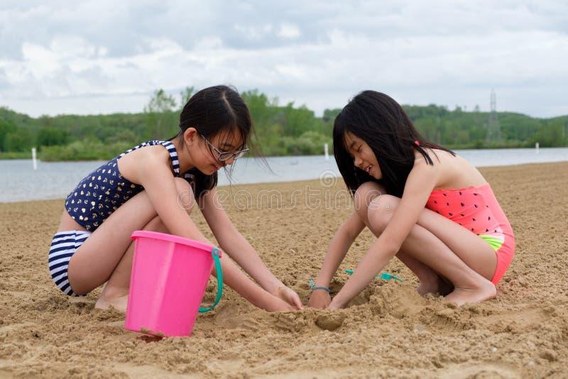 Twee kleine Aziatische meisjes die zand spelen bij strand stock afbeelding