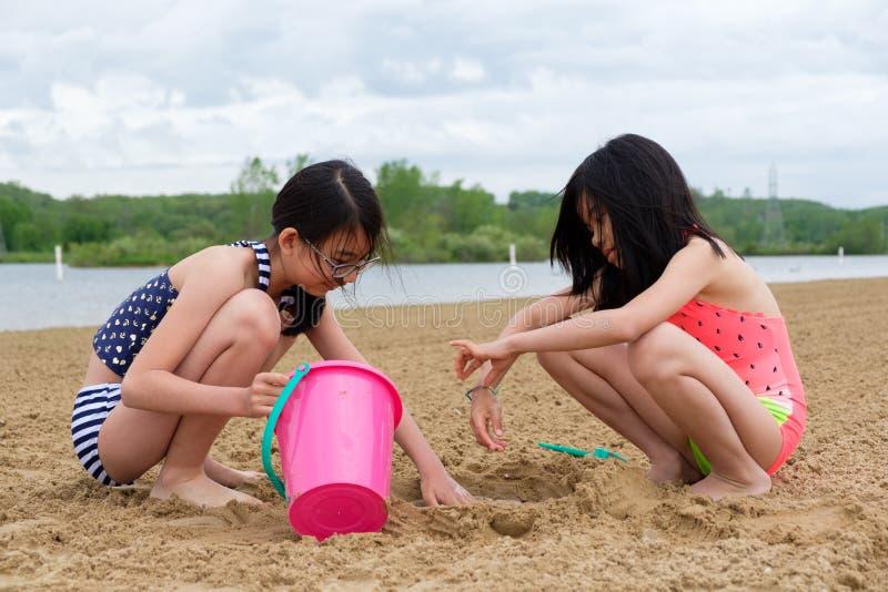Twee kleine Aziatische meisjes die zand spelen bij strand stock foto