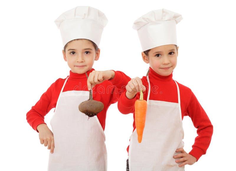Twee kleine belangrijkst-kooktoestellen die groenten houden stock foto's