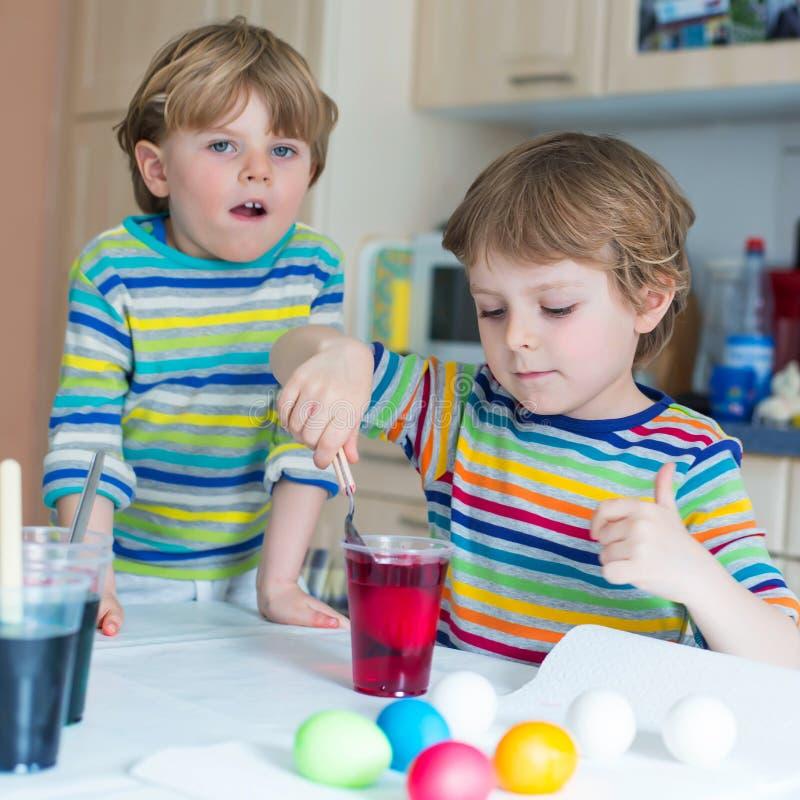 Twee kleine blonde jong geitjejongens die eieren voor Pasen-vakantie kleuren royalty-vrije stock fotografie