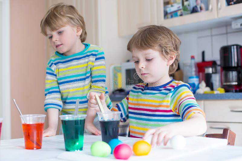 Twee kleine blonde jong geitjejongens die eieren voor Pasen-vakantie kleuren stock afbeeldingen