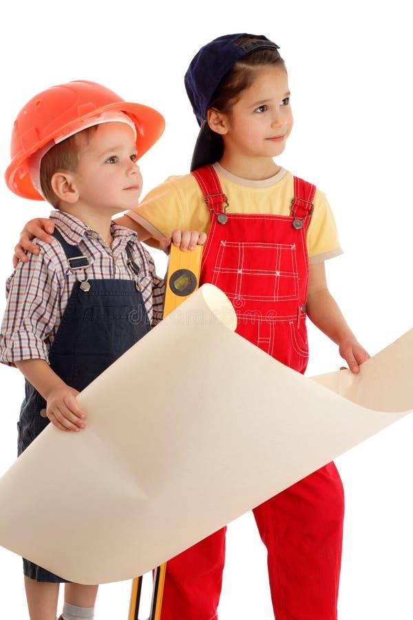 Twee kleine bouwers die met blauwdruk plannen royalty-vrije stock afbeeldingen