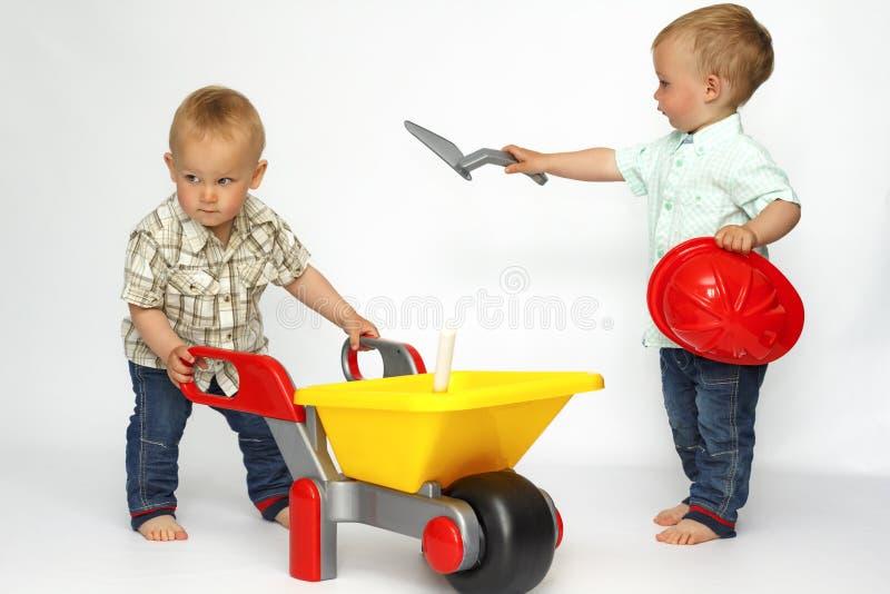 Twee kleine bouwers van het jongensspel royalty-vrije stock afbeeldingen
