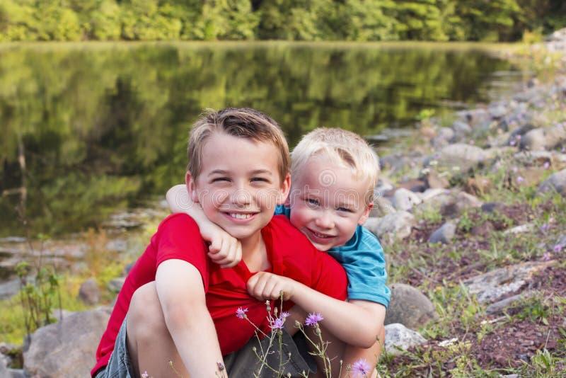 Twee kleine broers die bij het meer of de rivier op warme zonnige dag koesteren royalty-vrije stock afbeeldingen