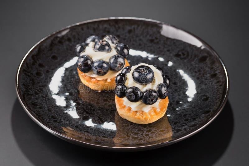 Twee kleine cakes met bosbessen en romige room op een zwarte plaat Hoogste mening royalty-vrije stock afbeeldingen