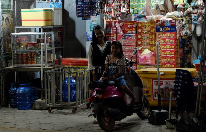 Twee kleine Cambodjaanse meisjes dichtbij een scooter Weinig straatwinkel Gelukkige Glimlachende Kinderen royalty-vrije stock fotografie
