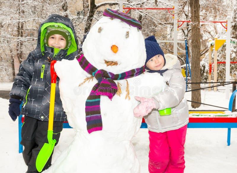 Twee kleine duivels, jonge geitjes die een sneeuwman maken, en pret met sneeuw, openlucht op koude dag spelen hebben Actieve in o stock afbeeldingen