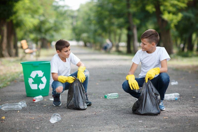 Twee kleine ecologisten die en plastic vuilnis op een vage parkachtergrond zitten verzamelen Het concept van de ecologiebeschermi stock fotografie