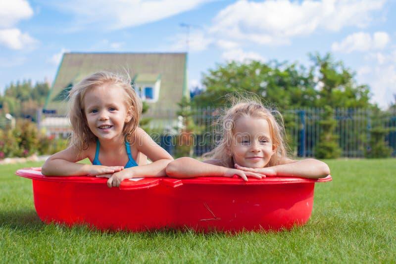 Twee kleine en zusters die binnen frolicing bespatten royalty-vrije stock afbeelding