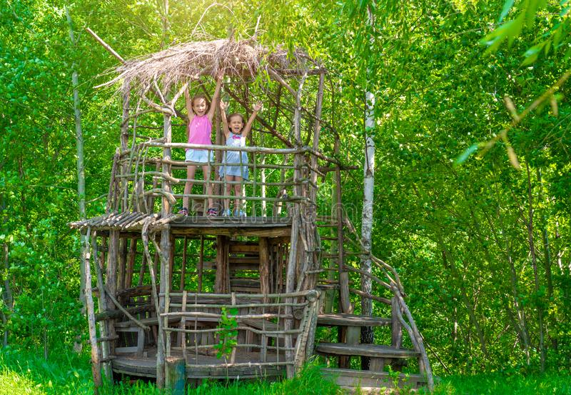 Twee kleine gelukkige meisjes in een houten boomhuis op een zonnige dag De zusters verheugen zich in de zomer Het concept de zome stock foto's