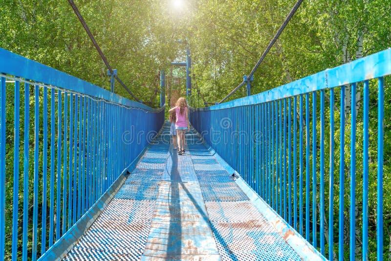 Twee kleine gelukkige meisjesgang langs een hangende brug op een zonnige dag royalty-vrije stock afbeeldingen
