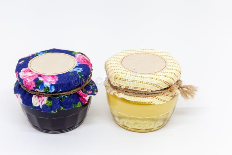 Twee kleine glaskruiken honing en jam royalty-vrije stock foto's