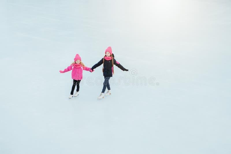 Twee Kleine glimlachende meisjes die op ijs in roze slijtage en hand schaatsen - gemaakte sjaals openlucht De winter royalty-vrije stock foto