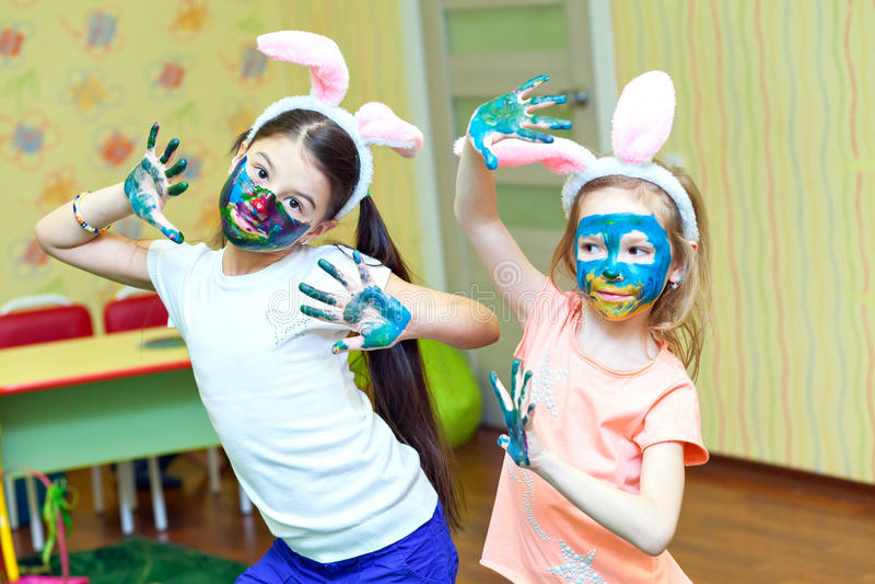 Twee kleine grappige meisjesverf gekleurde verf op zijn gezicht stock fotografie