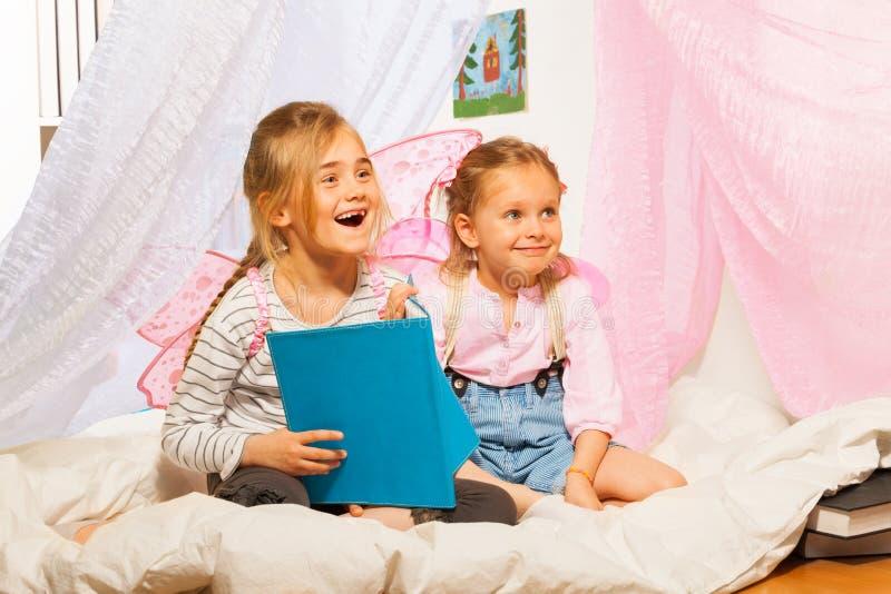 Twee kleine het glimlachen elf die het sprookje lezen royalty-vrije stock foto