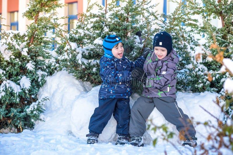 Twee kleine jong geitjejongens die in kleurrijke kleren in openlucht tijdens sneeuwval spelen Actieve vrije tijd met kinderen in  royalty-vrije stock foto's