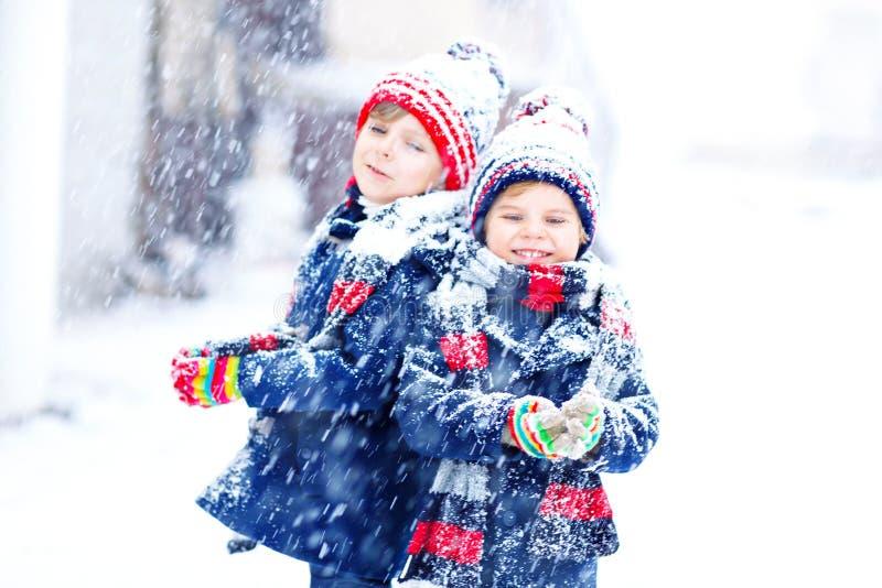 Twee kleine jong geitjejongens die in kleurrijke manierkleren in openlucht tijdens sterke sneeuwval spelen Actieve vrije tijd met royalty-vrije stock fotografie