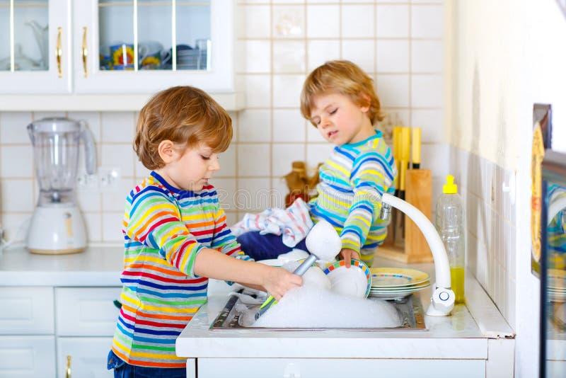 Twee kleine jong geitjejongens die schotels in binnenlandse keuken wassen royalty-vrije stock afbeelding