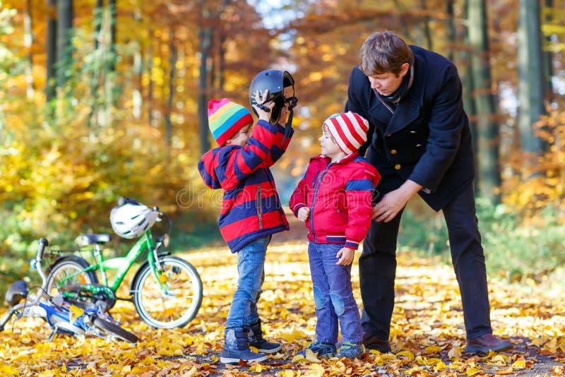 Twee kleine jong geitjejongens en vader met fietsen in de herfstpark stock foto