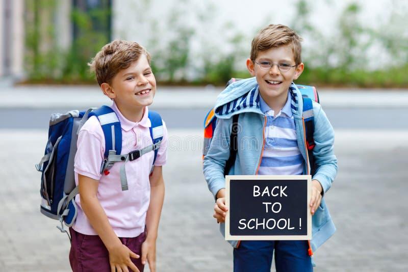 Twee kleine jong geitjejongens met rugzak of schooltas Schoolkinderen op de manier aan school Gezonde kinderen, broers en best royalty-vrije stock foto's