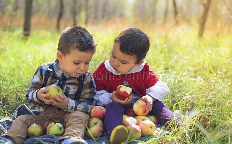 Twee kleine jonge geitjes die appelen in het park in de herfst eten stock afbeelding
