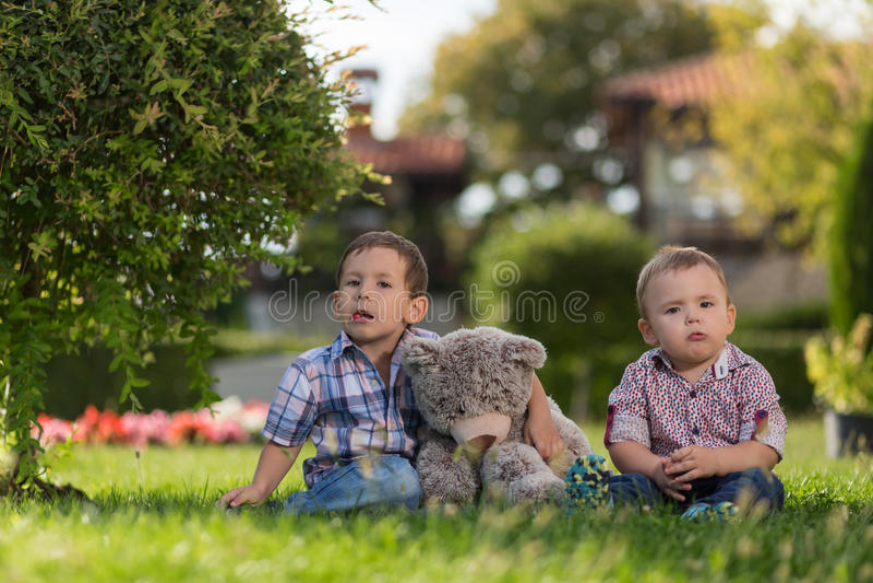 Twee kleine jonge geitjes die in de tuin spelen royalty-vrije stock afbeelding