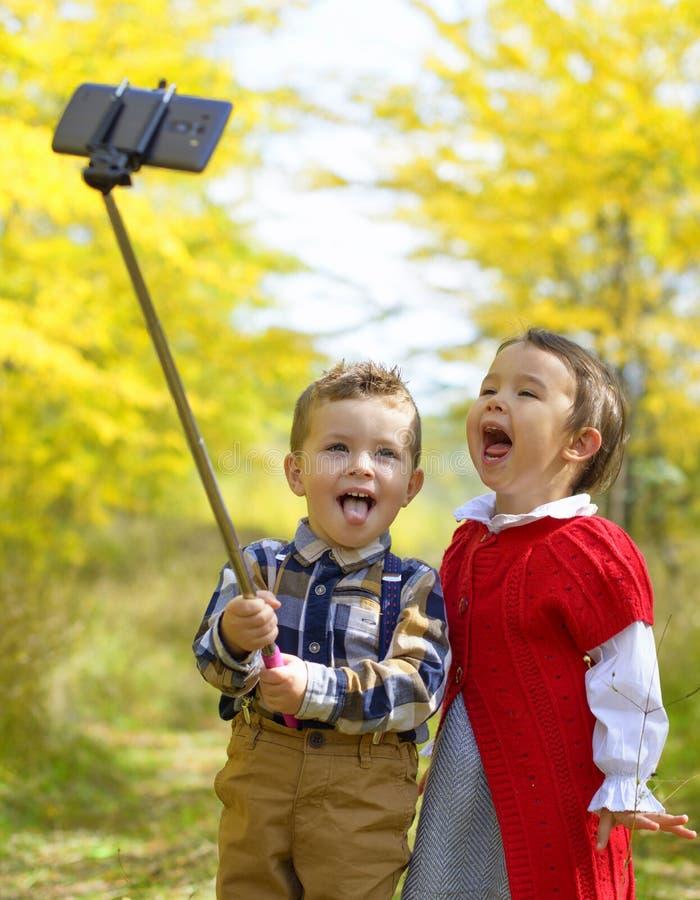Twee kleine jonge geitjes die selfie in park in de herfst nemen royalty-vrije stock afbeelding