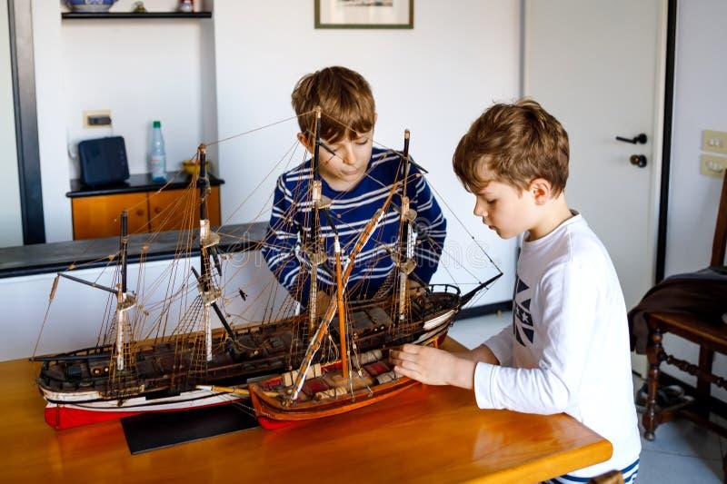 Twee kleine jonge geitjesjongens die met varend schipmodel binnen spelen Opgewekte kinderen, siblings en beste vrienden met jacht stock afbeeldingen