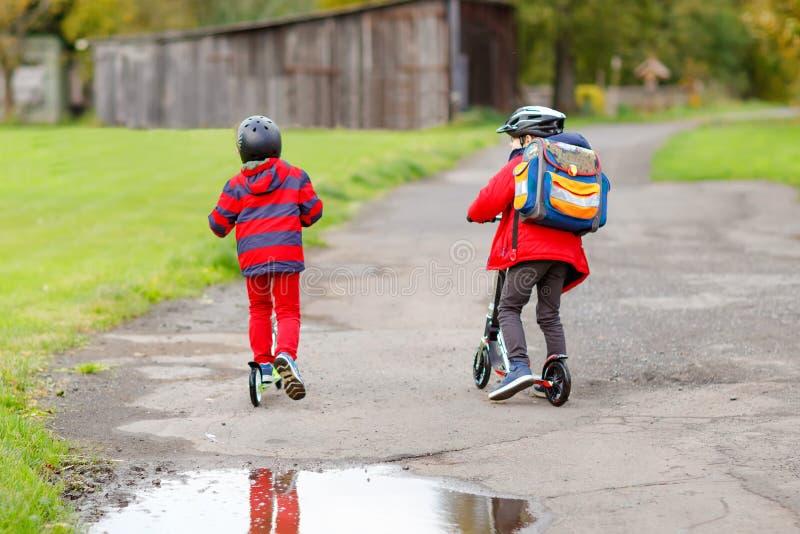 Twee kleine jonge geitjesjongens die op duwautopedden op de manier aan of van school berijden Schooljongens van 7 jaar die door r stock foto