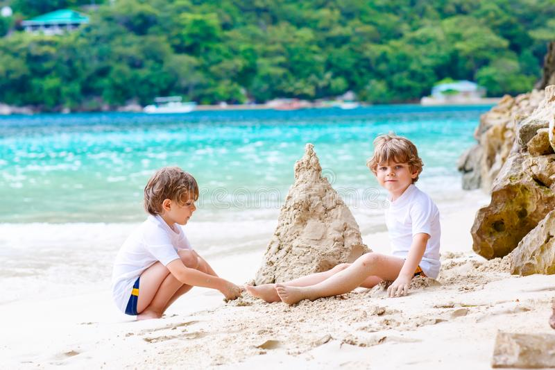 Twee kleine jonge geitjesjongens die pret met de bouw van een zandkasteel op tropisch strand van Seychellen hebben Kinderen die s stock foto's