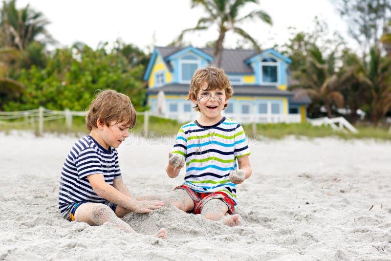 Twee kleine jonge geitjesjongens die pret met de bouw van zandkasteel op tropisch strand hebben royalty-vrije stock foto's