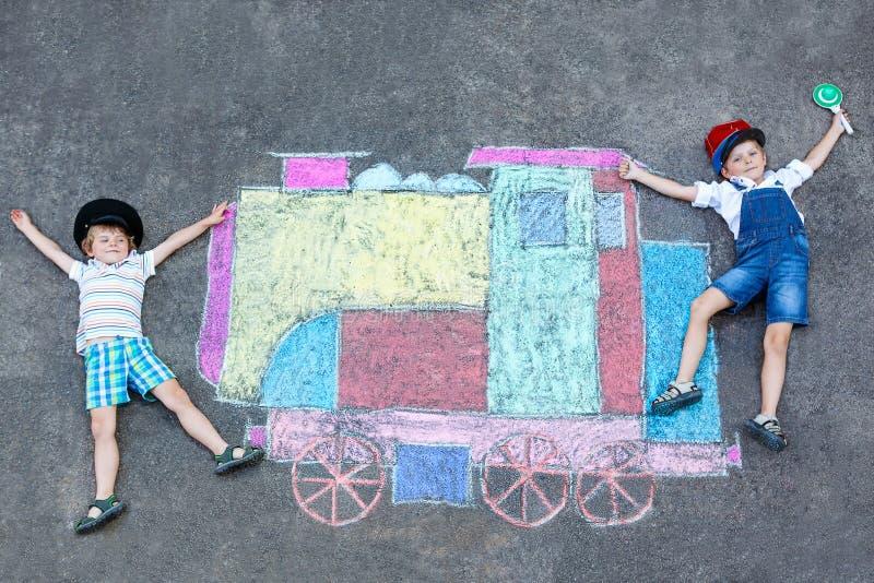 Twee kleine jonge geitjesjongens die pret met het beeld van het treinkrijt hebben royalty-vrije stock fotografie