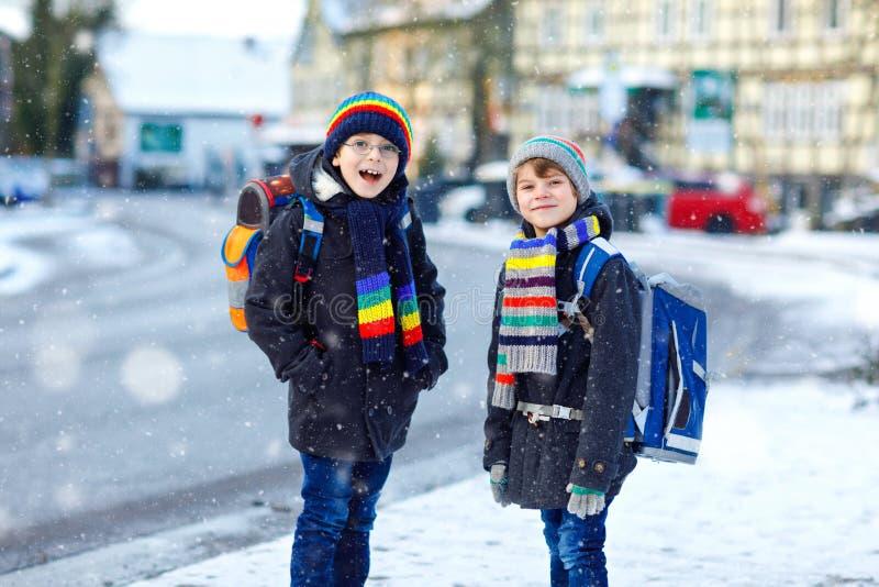 Twee kleine jonge geitjesjongens die van elementaire klasse aan school tijdens sneeuwval lopen Gelukkige kinderen die pret hebben stock afbeelding