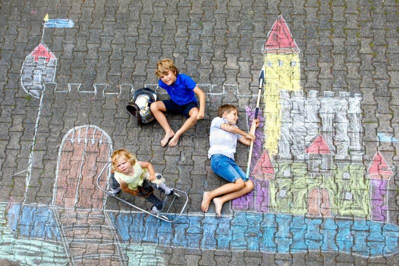 Twee kleine jonge geitjesjongens en het leuke kasteel van de de tekeningsridder van het peutermeisje met kleurrijk krijt op asfal royalty-vrije stock afbeelding