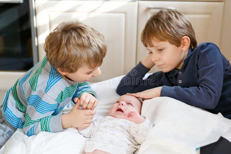 Twee kleine jonge geitjesjongens met pasgeboren babymeisje, leuke zuster siblings Broers en baby het spelen met kleurrijk speelgo stock afbeelding