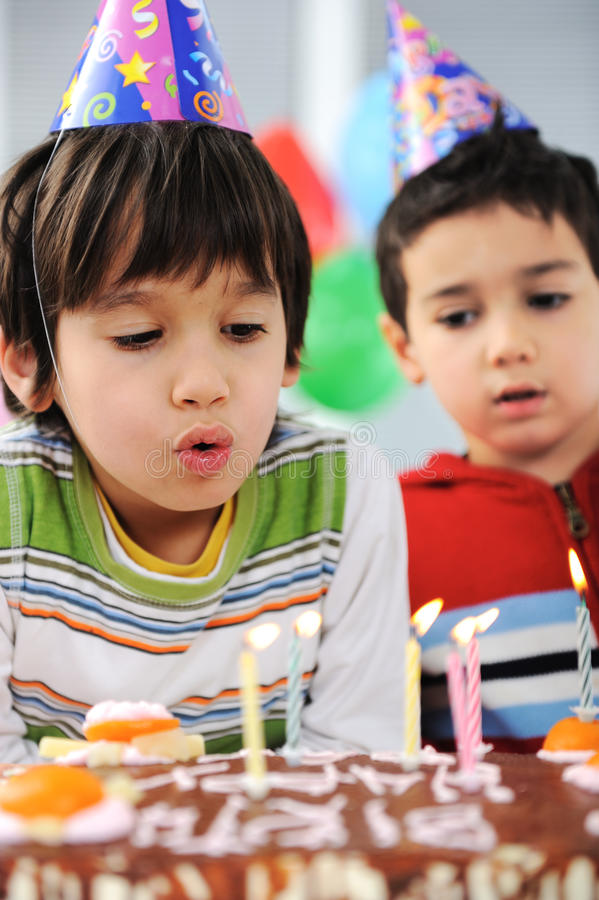 Twee kleine jongens die kaarsen op cake blazen royalty-vrije stock fotografie