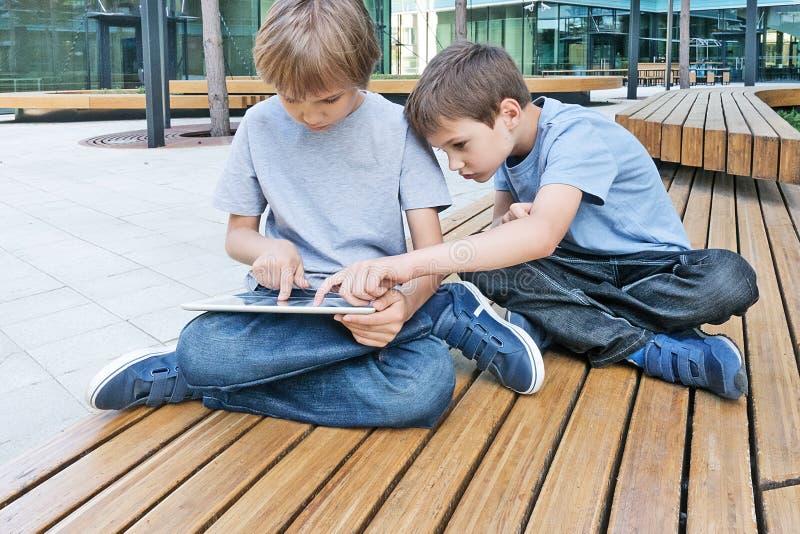 Twee kleine jongens die met tabletpc spelen, in openlucht stock afbeeldingen